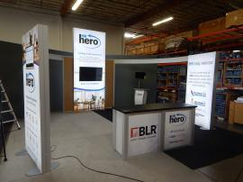RENTAL: Modified RE-9096 Island with (3) Double-Sided Lightboxes, Curved Bridged Extrusion Headers, RE-1207 Large Rectangular Counter, (2) RE-1213 Counter Kiosks, Silicone Edge Fabric Graphics for Lightboxes, and Direct Print Sintra Graphics for Counters
