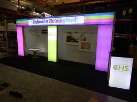 RENTAL: Custom Design with Backlit Header and Columns, Tension Fabric Backwall, RE-703 Charging Station, RE-1566 Backlit Reception Counter, and Direct Print Stand-Off Graphics